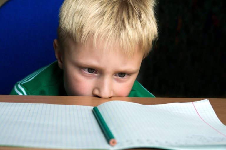 Frustrated boy with head on table unable to concentrate on his homework
