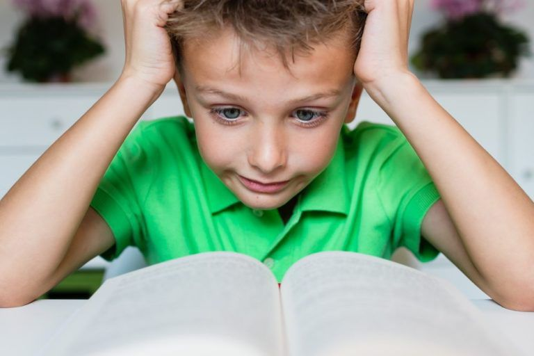 Child with learning disorder, frustrated in front of book